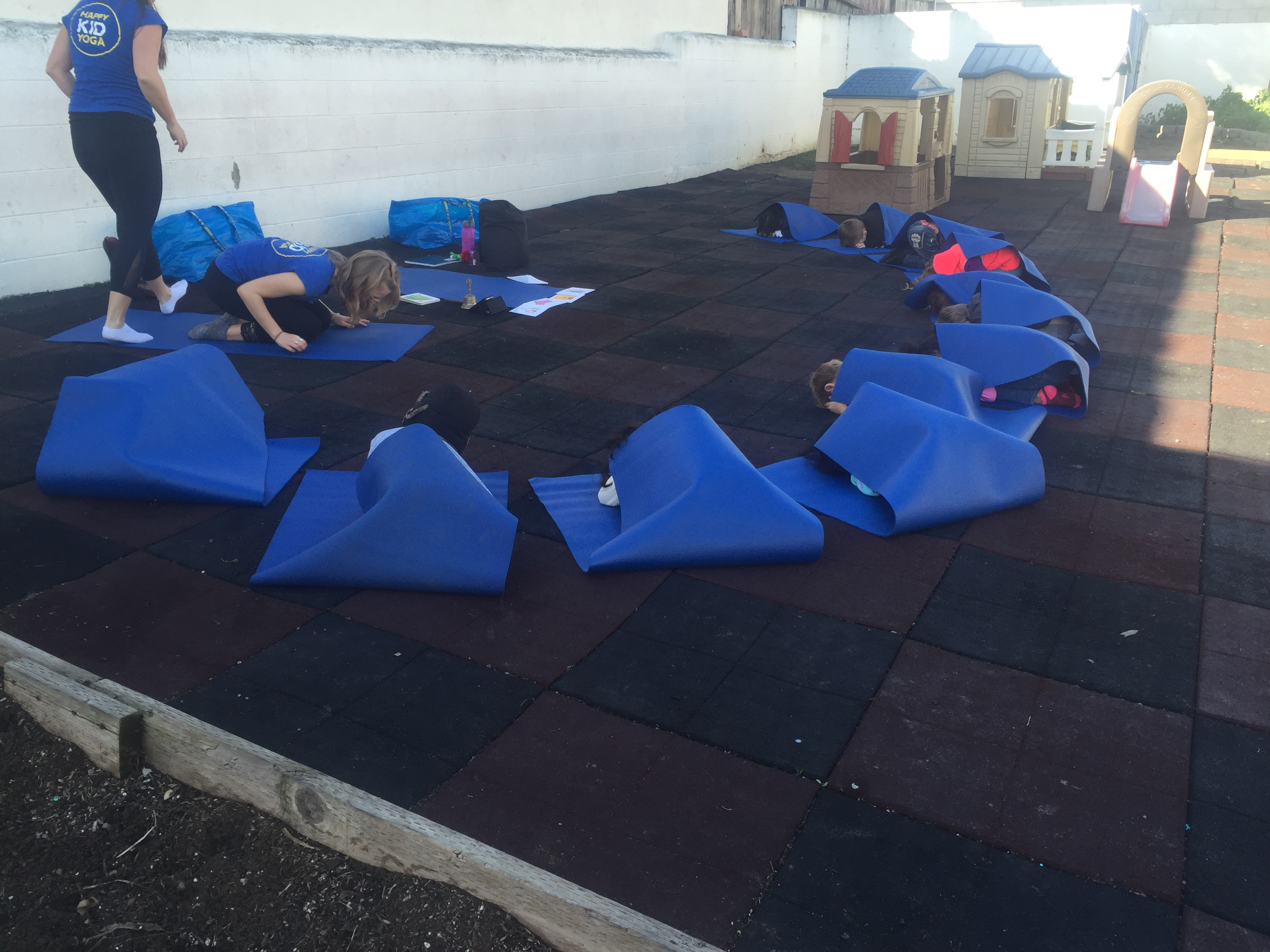 Happy Kid Yoga class with mats folded over the students like cocooned caterpillars